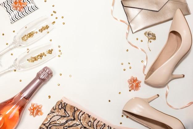Accessori donna per la festa: scarpe, occhiali, vestiti, regali su sfondo bianco.