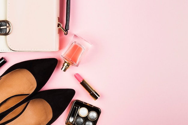 Accessori donna - scarpe, borsa, cosmetici, profumo su sfondo rosa