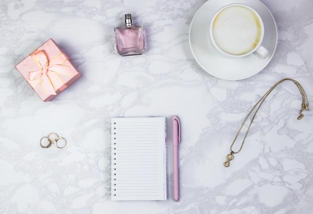 Accessori donna su un tavolo di marmo bianco. blocco note, penna e bicchiere di caffè sul tavolo e altri accessori cosmetici femminili. vista dall'alto, disteso, copia spazio