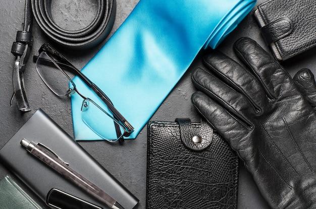 Accessori e abbigliamento da uomo su sfondo nero di cemento. concetto di successo uomo.