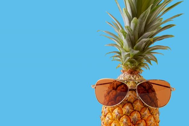 Accessori e frutta di modo dell'ananas dei pantaloni a vita bassa su fondo blu