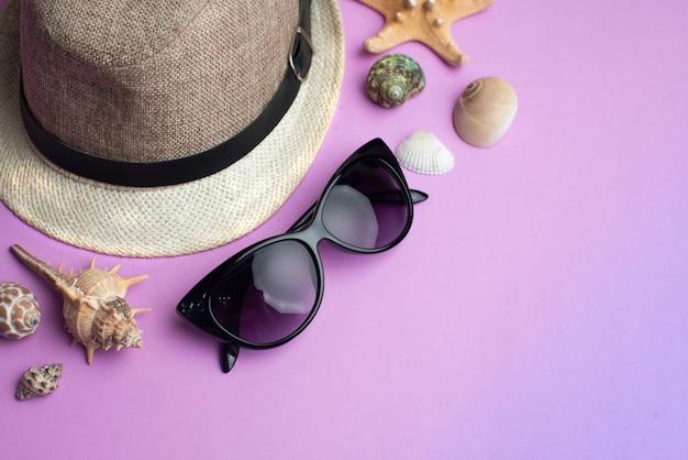 Accessori estate, conchiglie, cappello e occhiali da sole su sfondo rosa. vacanze estive e concetto di mare.