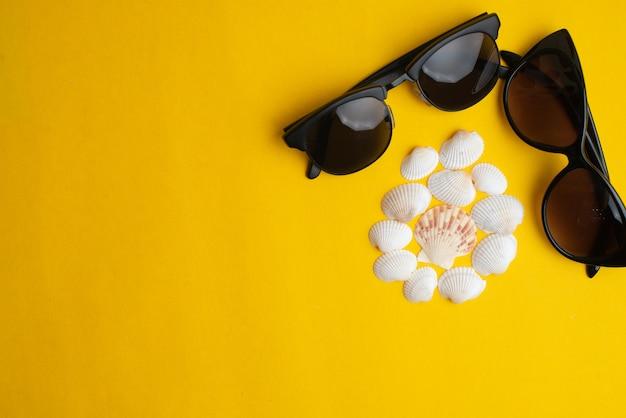 Accessori estivi, conchiglie e occhiali da sole coppia su superficie gialla.