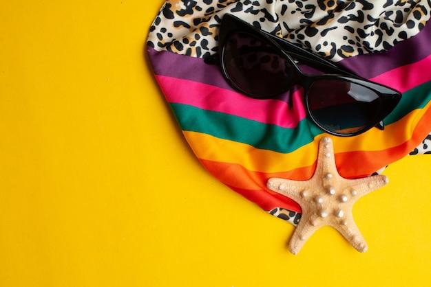 Accessori estivi, conchiglie, sciarpa e occhiali da sole. vacanze estive e concetto di mare.