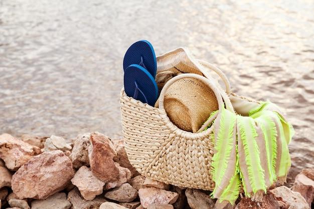 Accessori estivi raccolti in una borsa di paglia sulla riva al tramonto