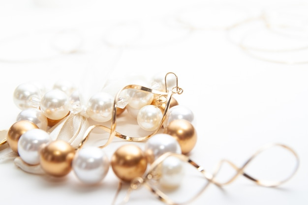 Accessori gioielli, bracciali, anelli, orecchini su bianco.
