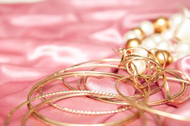Accessori gioielli, bracciali, anelli, orecchini su tessuto rosa