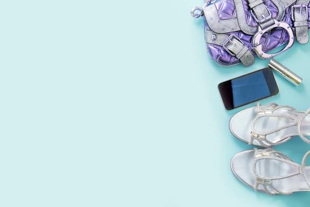 Accessori moda scarpe borsa telefono gadget sfondo azzurro