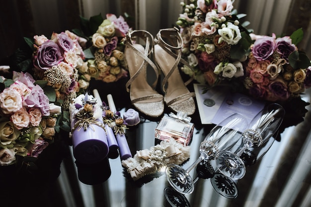 Accessori nuziali nuziali nei colori rosa e viola, bicchieri da champagne cerimoniali, bouquet da sposa per sposa e damigelle