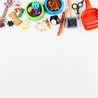 Accessori per animali e dolcetti su superficie bianca