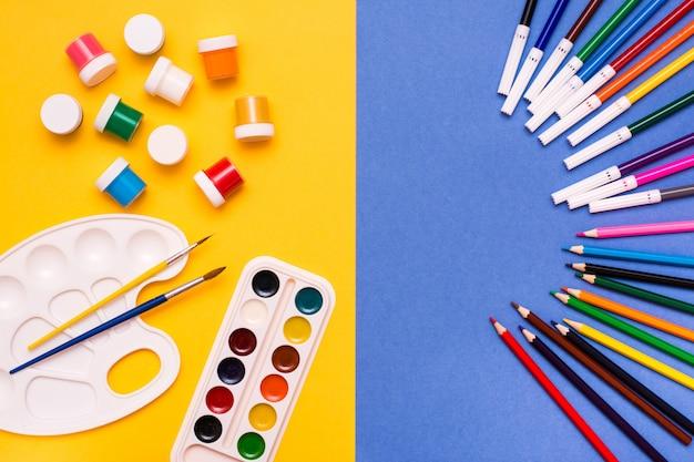 Accessori per disegnare matite, pennarelli, acquerelli, tempere e pennelli su un gialloblu