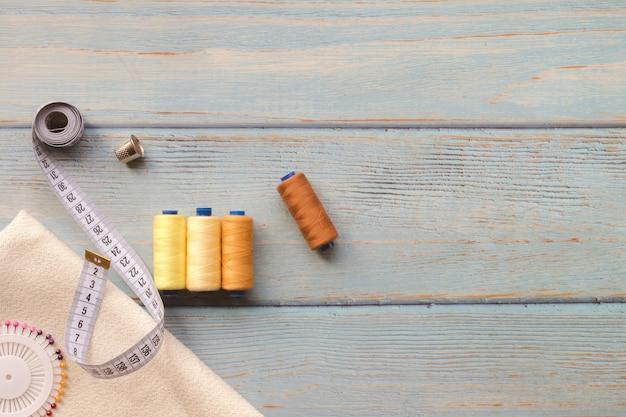 Accessori per il cucito e tessuto su sfondo blu. tessuto, fili per cucire, ago e centimetro per cucire. vista dall'alto, flatlay, copyspace