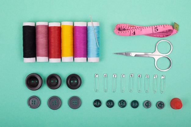 Accessori per kit da cucire strumenti set per adattamento e fili colorati, aghi, spille, forbici su sfondo verde vista dall'alto.