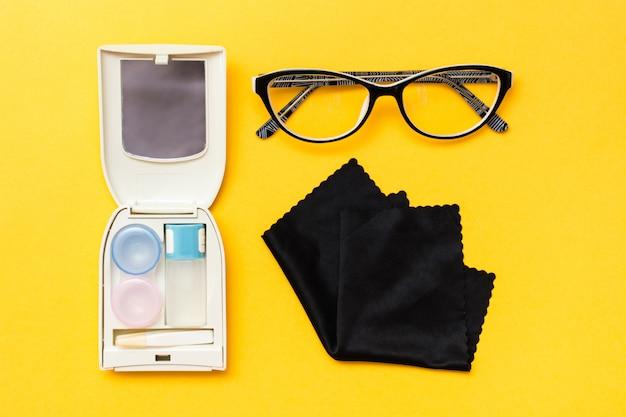 Accessori per la conservazione delle lenti: una bottiglia di liquido, un contenitore e una pinzetta in una custodia, occhiali e panno per la pulizia