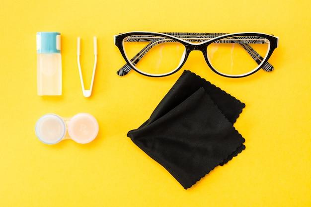Accessori per la conservazione delle lenti: una bottiglia di liquido, un contenitore e una pinzetta, occhiali e un panno