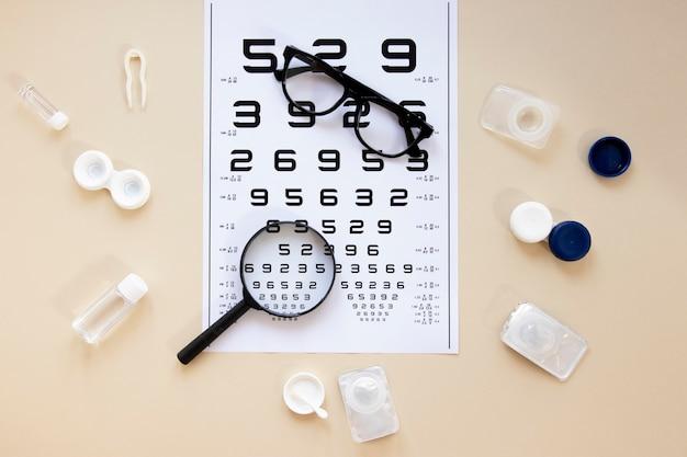Accessori per la cura degli occhi vista dall'alto su sfondo beige con tabella dei numeri