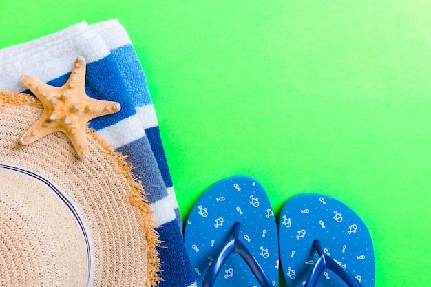 Accessori per la posa piatta da spiaggia estiva. cappello di paglia crema solare, infradito, asciugamano e conchiglie. concetto di vacanza viaggio con spazio di copia