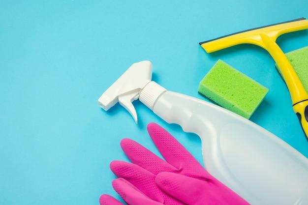 Accessori per la pulizia e pulizia, guanti, spray, spugne, raschietto per finestre su sfondo blu. concetto di servizio di pulizia. vista piana, vista dall'alto