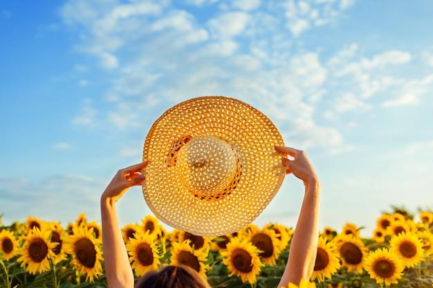 Accessori per le vacanze estive. la donna che cammina nel giacimento di girasole di fioritura ha sollevato il cappello su