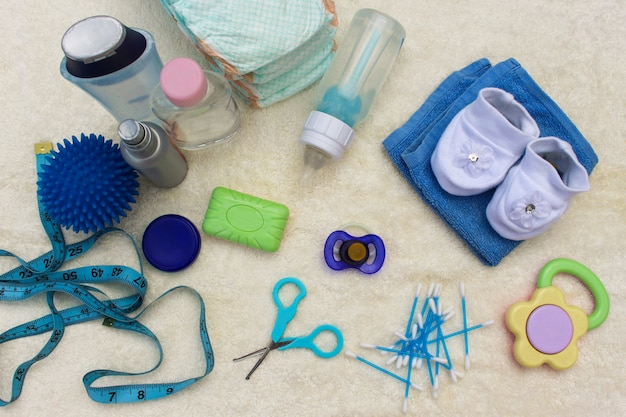 Accessori per neonati: ciuccio, bottiglia, pannolini usa e getta, forbici, fondi per il bagno, la palla per il massaggio, metro per misurare la crescita del bambino, pettine, olio per il corpo