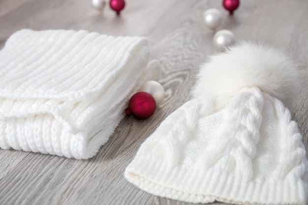 Accessorio per la stagione fredda lavorato a maglia vicino alle sfere dell'albero di capodanno.