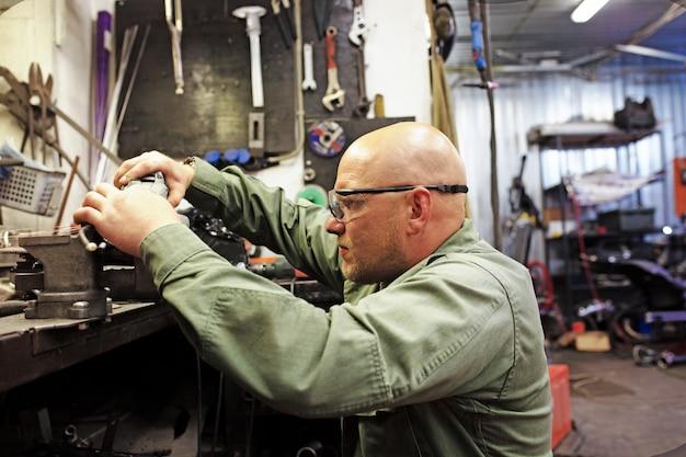 Acciaio di taglio del lavoratore dell'industria pesante con la smerigliatrice di angolo al servizio dell'automobile