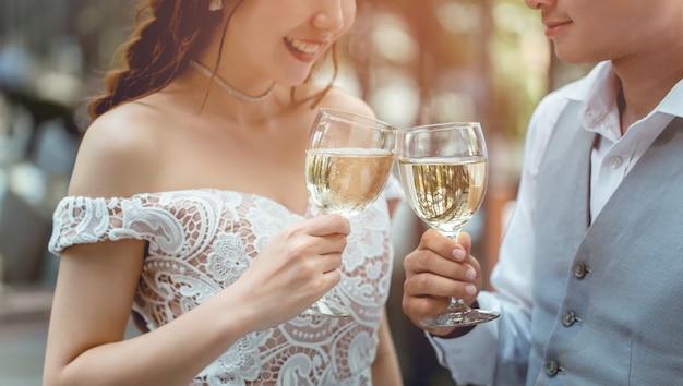 Acclamazione asiatica delle coppie che beve insieme nel ristorante.