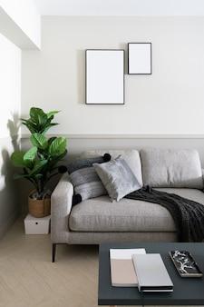 Accogliente angolo soggiorno con divano in tessuto di velluto grigio scuro, piante artificiali e cornice vuota installata sul muro