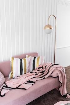 Accogliente angolo soggiorno con divano in velluto rosa e lampada da terra dorata in stile classico moderno in cima con soffice coperta rosa con parete a strisce di legno bianco
