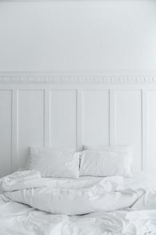 Accogliente camera da letto con due cuscini e una coperta disordinata sul muro dipinto di bianco