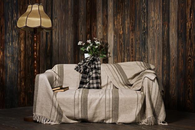 Accogliente camera in legno con divano coperto con plaid e libri su di esso. lampada da terra vintage in sala lettura.
