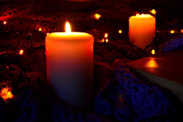 Accogliente casa di fondo con un plaid e candele di notte. candele accese e luci di natale.