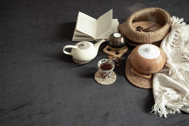 Accogliente casa in natura morta con dettagli decorativi all'interno. articoli per la casa e comfort. candele e un libro giacciono sul letto in soggiorno.