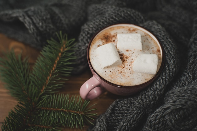 Accogliente casa invernale. tazza di cacao con marshmallow, calda sciarpa lavorata a maglia e rametto di albero di natale sul tavolo di legno marrone.