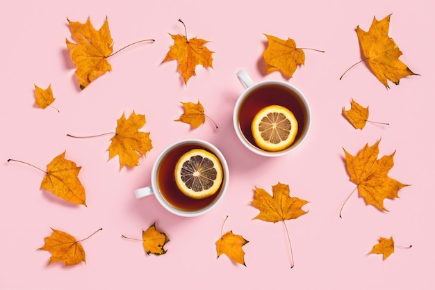 Accogliente composizione autunnale. due tazze da tè con fettine di limone e foglie di acero.