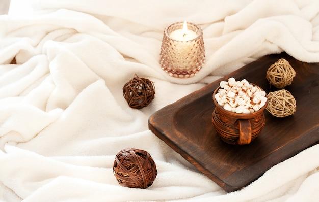 Accogliente hygge scandinavo con candela accesa, tazza di bevanda con marshmallow su morbida coperta bianca.