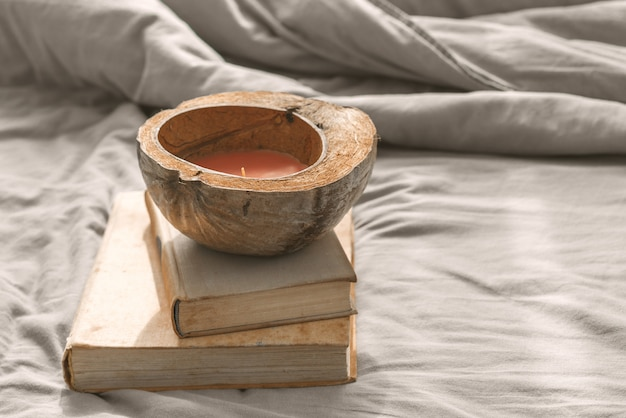 Accogliente letto disordinato, biancheria da letto grigia con libri e candele conchiglie di cocco.