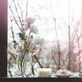 Accogliente natura morta primaverile: tazza di tè caldo con bouquet primaverile di fiori sul davanzale vintage con marshmallow rosa. primavera. appartamento.