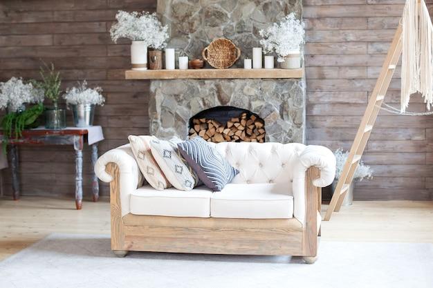 Accogliente salotto interno divano bianco e camino. design rustico per una vacanza alpina al caldo spazio interno. decorazione moderna del salone del cottage con la parete e la mobilia di legno. stile scandinavo. boho