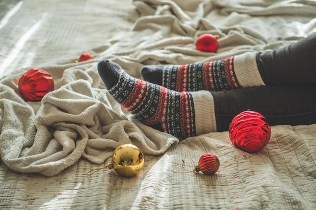 Accogliente sera autunno inverno, calze di lana calda. la donna è sdraiata sulla coperta irsuta bianca con i giocattoli di natale