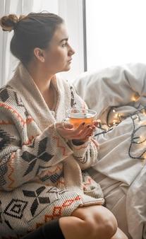 Accogliente tazza di tè trasparente a una ragazza carina in un caldo maglione lavorato a maglia contro la finestra