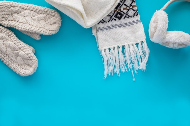 Accoglienti oggetti lavorati a maglia: una sciarpa, guanti, calde cuffie sul blu.