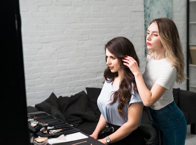 Acconciatura della regolazione del parrucchiere di giovane cliente femminile