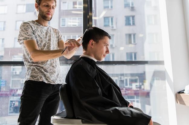Acconciatura e taglio di capelli da uomo in un barbiere o in un parrucchiere