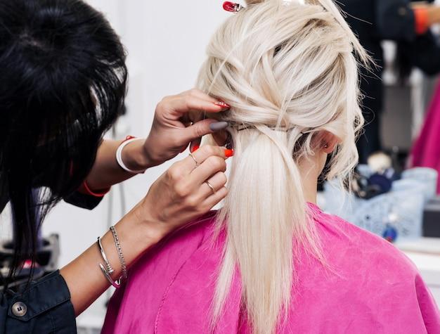 Acconciatura in un salone di bellezza per una ragazza bionda da un parrucchiere professionista