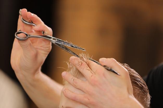 Acconciatura maschile, taglio di capelli, in un barbiere o parrucchiere.