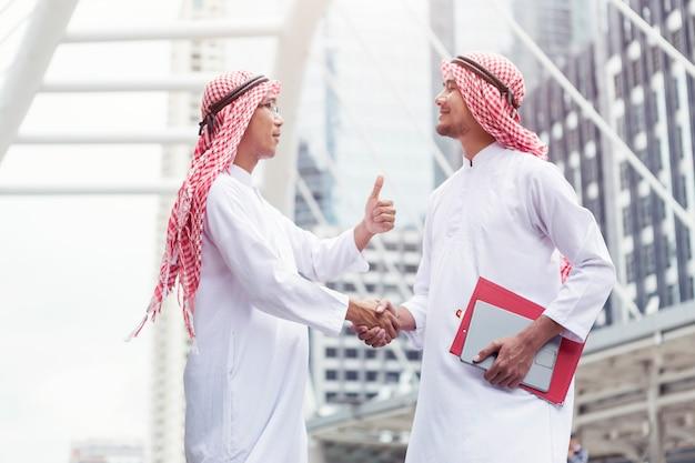 Accordo commerciale di successo, gli arabi si stringono la mano in città.