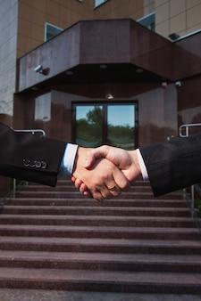 Accordo commerciale. stretta di mano su sfondo banca. si stringono la mano l'un l'altro. partner di amicizia.