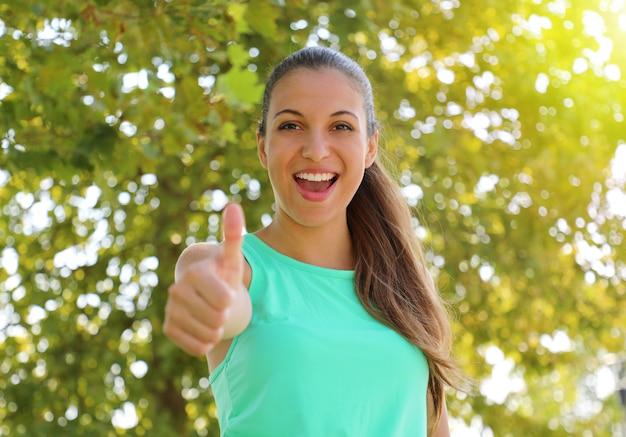 Accordo di bella donna fitness con il pollice in alto all'aperto con uno sfondo verde sfocato.