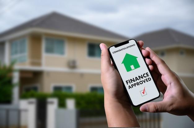 Accordo di prestito finanziario e approvazione di prestito ipotecario chiave della casa sul telefono cellulare in una casa